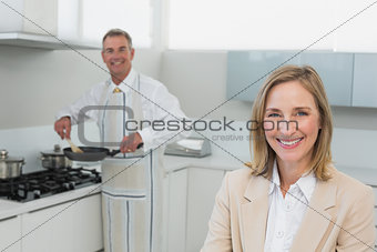 Businesswoman with man preparing food in kitchen
