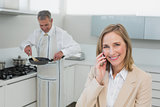 Businesswoman on call while man preparing food in kitchen