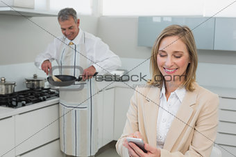 Businesswoman text messaging while man preparing food in kitchen