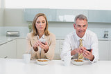 Business couple text messaging while having breakfast in kitchen