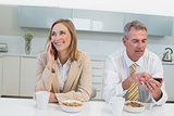 Business couple using cellphones while having breakfast in kitchen