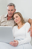Loving couple using laptop on sofa