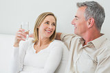 Couple with a glass of water in living room