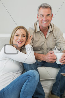 Portrait of couple with coffee cup in living room