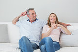 Happy relaxed couple sitting on sofa