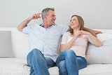 Happy relaxed couple sitting on sofa in living room
