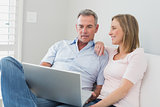 Relaxed couple using laptop on sofa