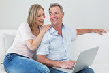 Relaxed couple using laptop at home
