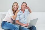 Portrait of a relaxed couple using laptop at home