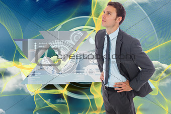 Composite image of serious businessman standing with hands on hips