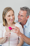Happy romantic couple with a flower at home