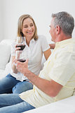 Relaxed couple with wine glasses sitting on sofa