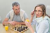 Couple playing chess while having orange juice
