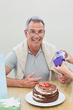 Portrait of a man receiving a gift by cake