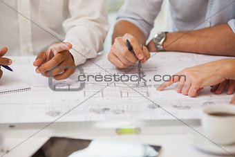 Mid section of business people working on blueprints