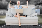 Composite image of cheering beautiful businesswoman sitting on couch