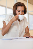Businesswoman drinking coffee while working on blueprint in office