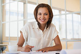 Smiling businesswoman working on blueprint in office