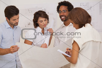 Group of architects working on blueprints