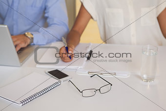 Close-up mid section of business people in meeting