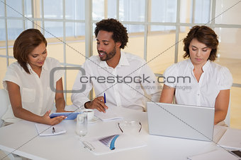 Business people using digital tablet and laptop in meeting
