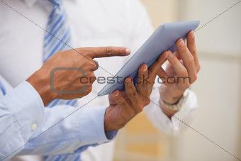 Mid section of businessmen using digital tablet