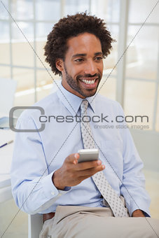 Smiling businessman with mobile phone looking away at office