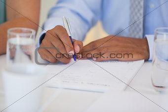Close-up mid section of a businessman writing document