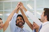 Cheerful business team joining hands together in office