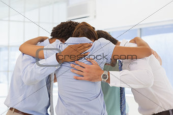 Business team with heads together forming a huddle