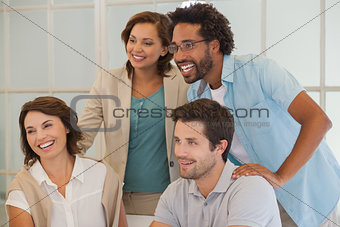 Smiling business people looking away at office
