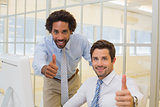 Smiling businessmen gesturing thumbs up in office