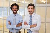 Two smiling businessmen with arms crossed in office