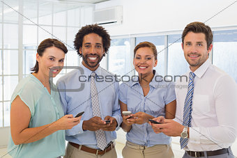 Smiling business colleagues text messaging in office
