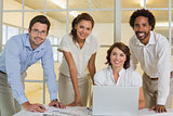 Happy business people using laptop in meeting at office