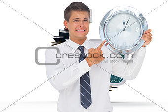 Composite image of anxious businessman holding and showing a clock