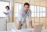 Businessman working on blueprints with colleague in background at office