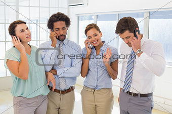 Business colleagues using mobile phone in office