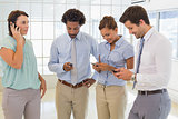 Business colleagues text messaging in office