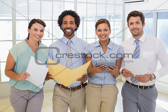 Business colleagues holding folders in office