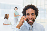 Smiling businessman on call with colleagues at office