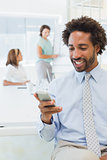 Businessman text messaging with colleagues in meeting at background