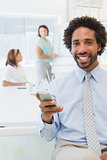 Smiling businessman text messaging with colleagues in office