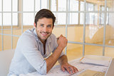 Smiling businessman working on blueprints in office