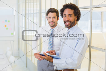 Two businessmen with digital tablet in office