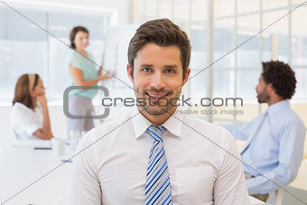 Smiling businessman with colleagues in meeting at office