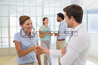 Business people shaking hands with colleagues in office