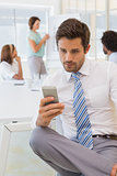 Businessman text messaging with colleagues in meeting