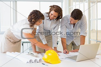 Business people working on blueprints in office