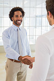 Smiling young businessmen shaking hands in office